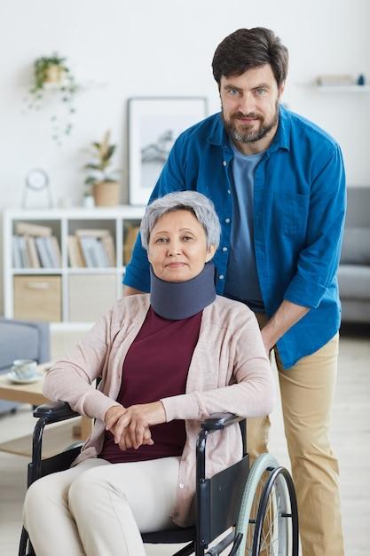 Porträt des reifen bärtigen mannes, der sich um behinderte ältere frau im rollstuhl zu hause kümmert Premium Fotos