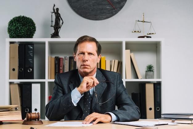 Porträt des reifen rechtsanwalts sitzend im gerichtssaal Kostenlose Fotos