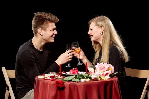 Porträt des romantischen paares, das weißwein beim abendessen röstet Kostenlose Fotos