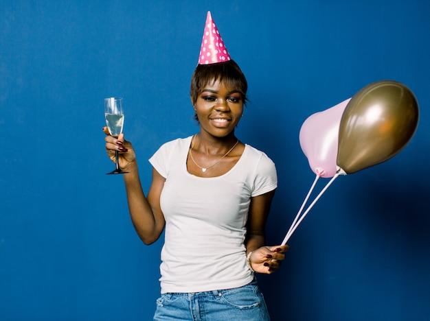 Porträt des schönen afrikanischen geburtstagsmädchens, das an der partei ruht. hübsches lächelndes afrikanisches mädchen, das glas mit champagner und luftballons hält, die auf blauem raum aufwerfen Premium Fotos