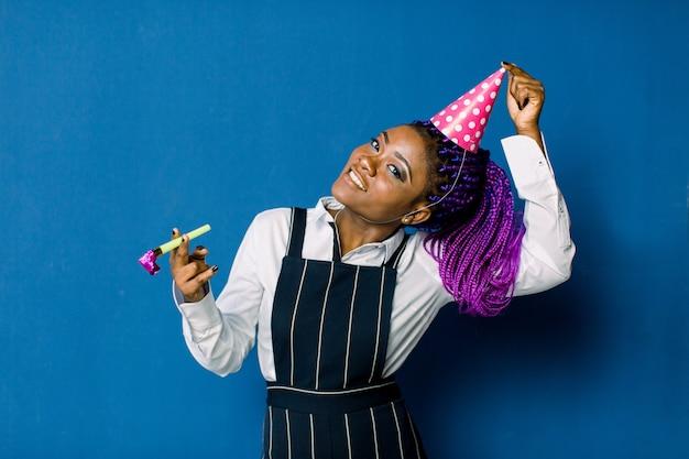 Porträt des schönen afrikanischen mädchens, das an der partei ruht. porträt der lustigen afrikanischen frau im geburtstagshut auf blauem raum. feier und party. Premium Fotos