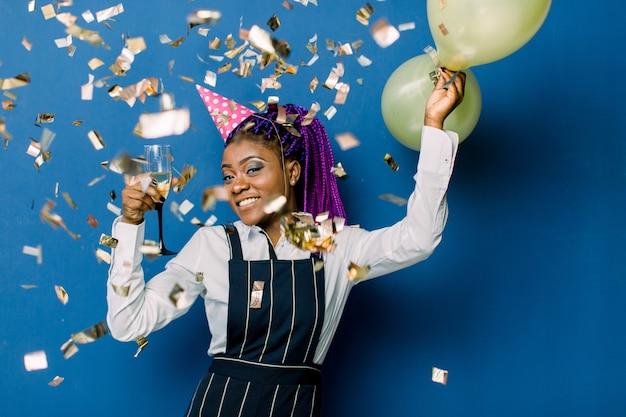 Porträt des schönen afrikanischen mädchens in der rosa partykappe, die luftballons und champagner hält, die an der partei ruhen. afrikanische frau, die spaß an der party mit konfetti auf blauem raum hat Premium Fotos