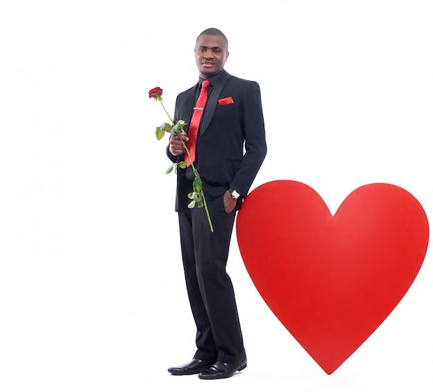 Porträt des schönen afrikanischen mannes, der rote rose, romantisches geschenk für valentinstag hält Kostenlose Fotos