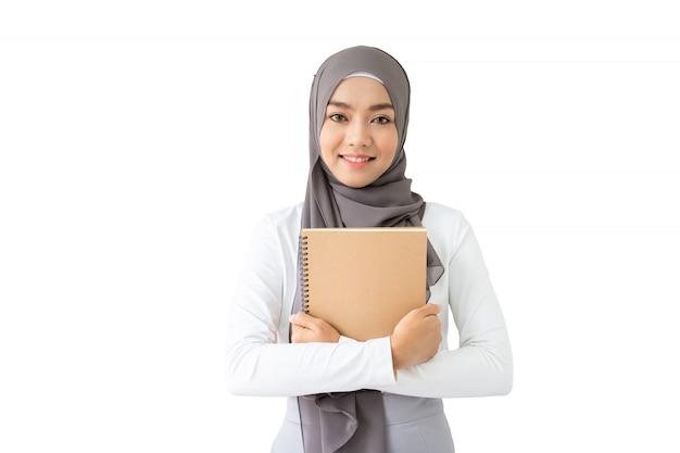 Porträt des schönen asiatischen moslemischen studenten, der ein buch und ein pencile, moslemisches studentendenken hält Premium Fotos