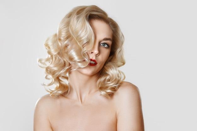 Porträt des schönen blonden mädchens mit dem gelockten haar, katzenaugenmake-up, rote lippen. konzept verspotten foto. Premium Fotos