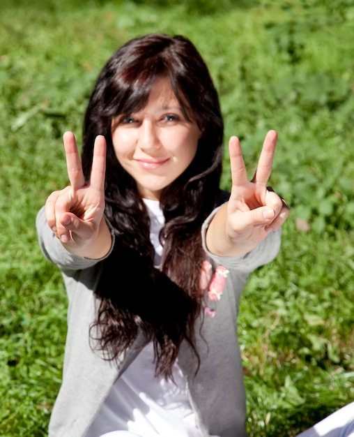 Porträt des schönen brunettemädchens mit blauen augen auf grünem gras im park, die hand v symb zeigen Premium Fotos