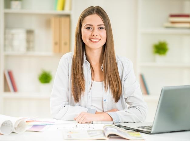 Porträt des schönen designers, der laptop in ihrem büro verwendet. Premium Fotos