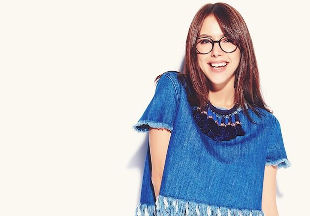 Porträt des schönen intelligenten lächelnden hipster-brünettenfrauenmodells in lässiger stilvoller blue jeans-kleidung und brille lokalisiert auf weiß Kostenlose Fotos