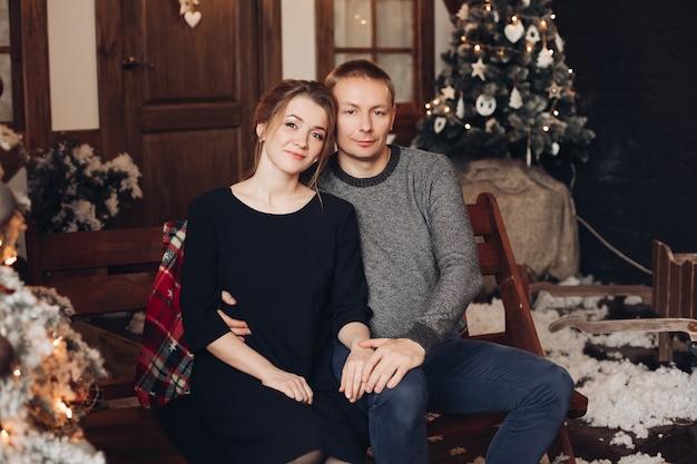 Porträt des schönen jungen erwachsenen paares, das sich auf holzbank im weihnachtsinnenraum kuschelt Premium Fotos
