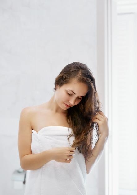 Porträt des schönen jungen weiblichen modells im bad, das haaröl anwendet. nahaufnahme der sexy frau im handtuch, das nasses langes haar trocknet. gesundheits- und schönheitskonzept. schutz feuchtigkeitscreme. Premium Fotos