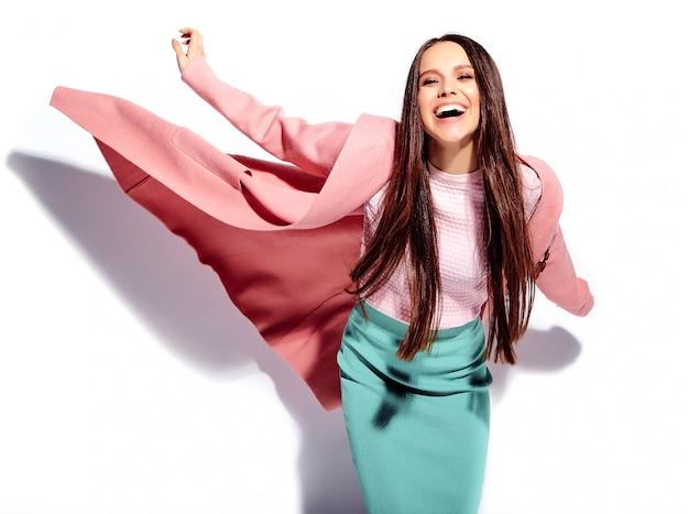 Porträt des schönen kaukasischen lächelnden brunettefrauenmodells im hellen rosa mantel und im stilvollen blauen rock des sommers Kostenlose Fotos