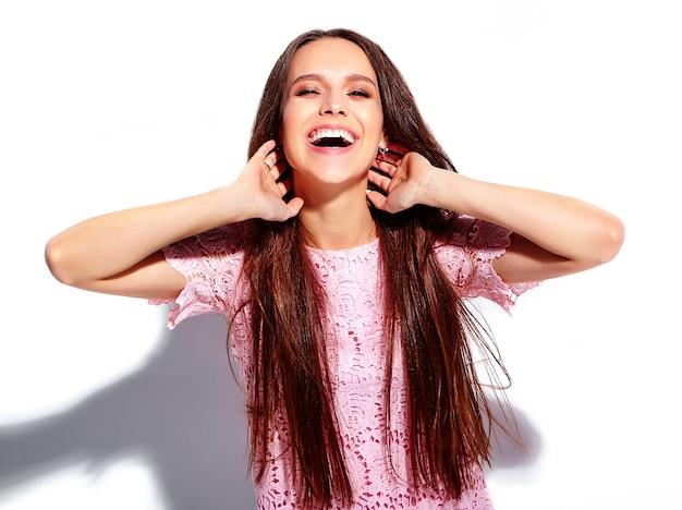 Porträt des schönen kaukasischen lächelnden brunettefrauenmodells im stilvollen kleid des hellen rosa sommers lokalisiert auf weißem hintergrund Kostenlose Fotos