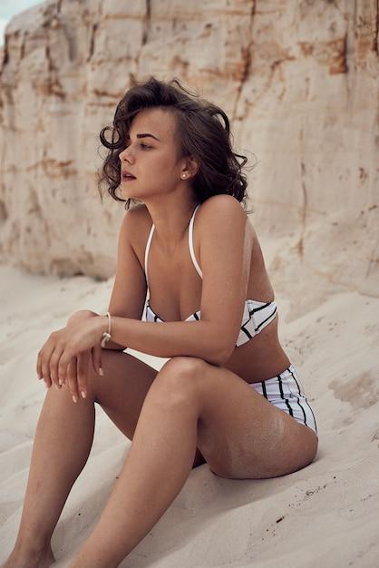 Porträt des schönen kaukasischen sonnenbad-frauenmodells mit dunklem langem haar im gestreiften badeanzug, der auf sommerstrand mit weißem sand liegt. draufsicht Premium Fotos