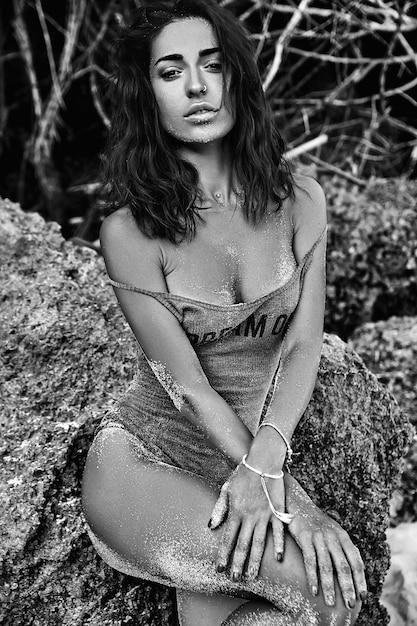 Porträt des schönen kaukasischen sonnengebadeten frauenmodells mit dem dunklen langen haar im badeanzug, der nahe felsen auf dem strand aufwirft Kostenlose Fotos