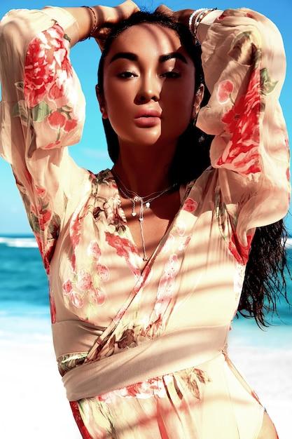 Porträt des schönen kaukasischen sonnengebadeten frauenmodells mit dem dunklen langen haar im beige fliegenkleid, das auf sommerstrand mit weißem sand auf blauem himmel und ozean aufwirft Kostenlose Fotos