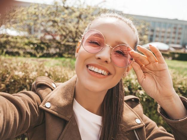 Porträt des schönen lächelnden brunettemädchens in der sommerhippie-jacke und in der jeanskleidung Kostenlose Fotos