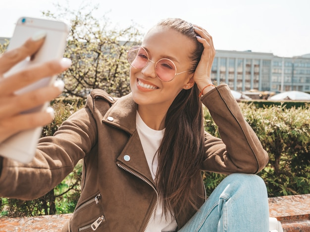 Porträt des schönen lächelnden brunettemädchens in der sommerhippie-jacke und -jeans modellieren das nehmen von selfie auf smartphone Kostenlose Fotos