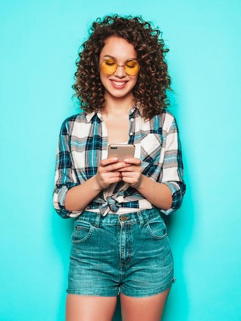 Porträt des schönen lächelnden modells mit afro-lockenfrisur gekleidet in sommerkleidung. sorgloses mädchen, das nahe blaue wand aufwirft. frau benutzt ihr handy und tippt sms. sie sucht nach ladenverkäufen Kostenlose Fotos