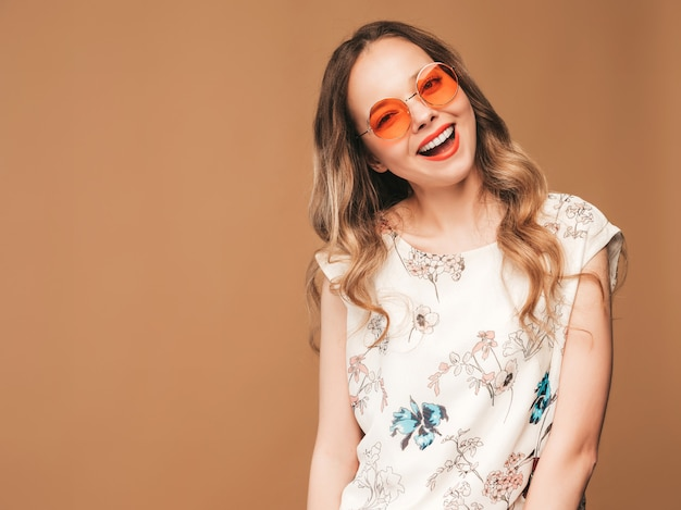 Porträt des schönen lächelnden netten modells mit den rosa lippen. mädchen im bunten kleid und in der sonnenbrille des sommers. model posiert Kostenlose Fotos