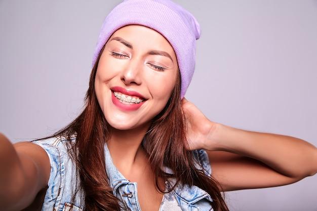 Porträt des schönen lächelnden niedlichen brünetten frauenmodells in der lässigen sommerjeanskleidung ohne make-up in der lila mütze, die selfie-foto am telefon lokalisiert auf grau macht Kostenlose Fotos