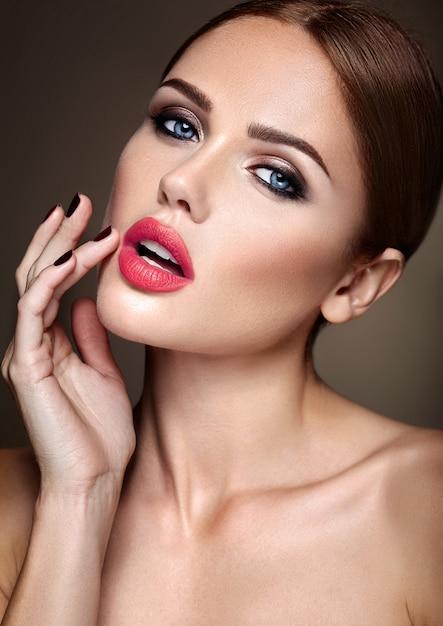 Porträt des schönen mädchenmodells mit abendmake-up und romantischer frisur. sie berührte ihre roten lippen Kostenlose Fotos