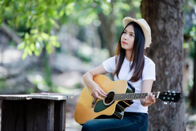 Porträt des schönen mädchens die gitarre mit dem schreiben an der natur spielend Kostenlose Fotos