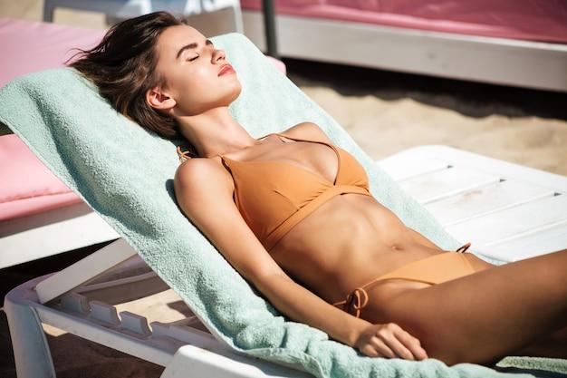 Porträt des schönen mädchens im bikini, das auf deckstuhl mit schließenden augen liegt, während zeit am strand verbringen. junge hübsche dame im beige badeanzug zum sonnenbaden und entspannen am strand Premium Fotos