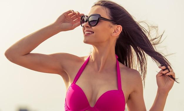 Porträt des schönen mädchens im rosa badeanzug und in den sonnenbrillen. Premium Fotos