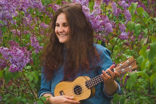 Porträt des schönen mädchens mit dem gelockten haar, welches die ukulele spielt Premium Fotos