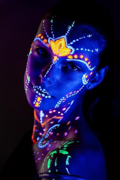Porträt des schönen mädchens mit ultravioletter farbe auf ihrem gesicht Premium Fotos
