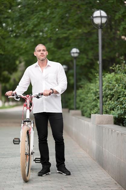 Porträt des schönen mannes mit dem fahrrad im freien Kostenlose Fotos