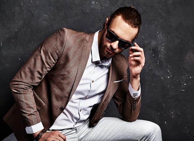 Porträt des schönen mode stilvollen hipster-geschäftsmannmodells gekleidet in elegantem braunem anzug, der nahe dunkelheit sitzt Kostenlose Fotos