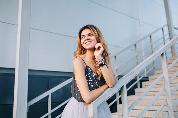 Porträt des schönen modells im grauen hemd, das auf handlauf auf treppen stützt. sie lächelt zur seite. Kostenlose Fotos