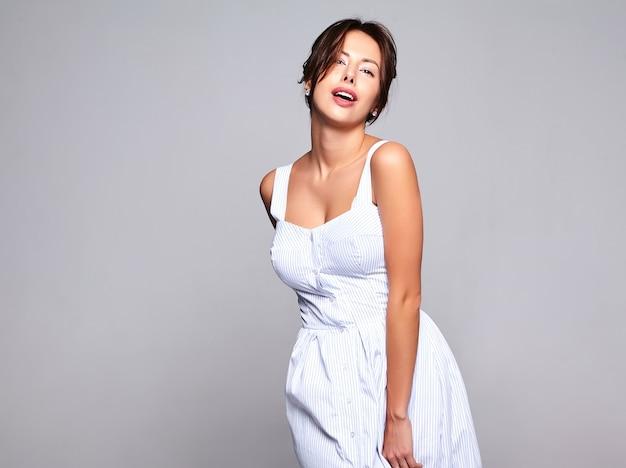 Porträt des schönen niedlichen brünetten frauenmodells im lässigen sommerkleid ohne make-up lokalisiert auf grau Kostenlose Fotos