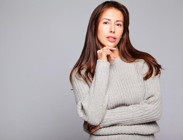 Porträt des schönen niedlichen brünetten frauenmodells in lässiger herbstgrauer pulloverkleidung ohne make-up lokalisiert auf grau Kostenlose Fotos