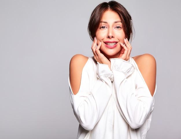 Porträt des schönen niedlichen brünetten frauenmodells in lässiger sommerkleidung ohne make-up lokalisiert auf grau Kostenlose Fotos