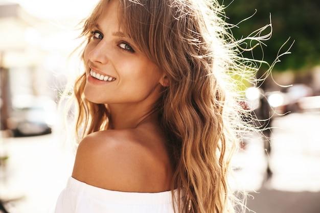 Porträt des schönen niedlichen lächelnden blonden teenagermodells ohne make-up im weißen sommer-hipster-kleid, das auf der straße hintergrund aufwirft. dreh dich um Kostenlose Fotos