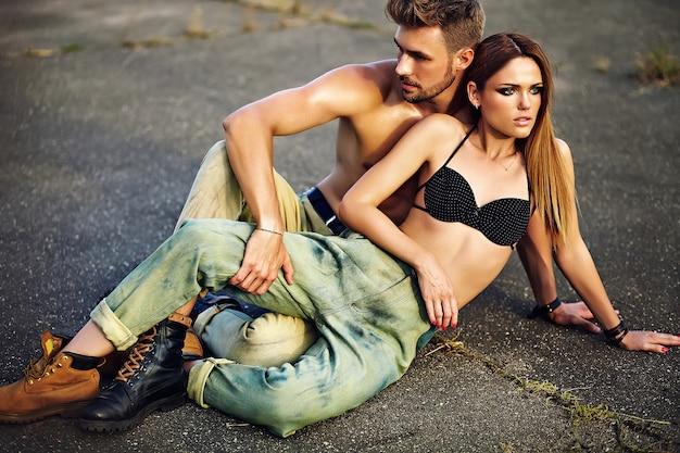 Porträt des schönen paares. sexy stilvolles blondes junges frauenmodell mit hellem make-up mit perfekter sonnengebadeter haut und hübschem muskulösem mann in den jeans draußen auf asphalthintergrund Kostenlose Fotos
