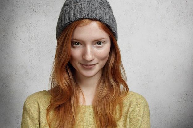 Porträt des schönen sommersprossigen mädchens mit langen roten haaren und niedlichem charmantem lächeln, das grauen stilvollen hut trägt, der gegen wand steht und lächelt Kostenlose Fotos
