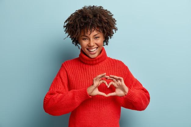 Porträt des schönen weiblichen modells macht herzgeste, sagt mein valentinstag, zeigt liebeszeichen Kostenlose Fotos