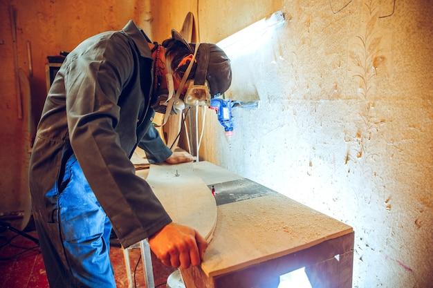 Porträt des schönen zimmermanns, der mit hölzernem schlittschuh an werkstatt arbeitet, profilansicht Kostenlose Fotos