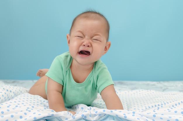 Porträt des schreienden asiatischen jungen des babys des umkippens auf bett Premium Fotos