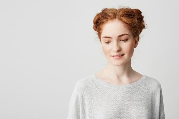 Porträt des schüchternen jungen hübschen rothaarigen mädchens mit brötchen, die lächelnd nach unten schauen. Kostenlose Fotos