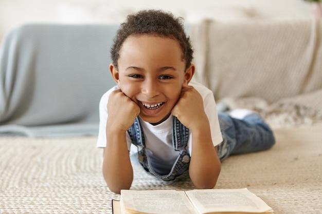 Porträt des schülers, der auf boden liegt und ein buch in der bibliothek in der schule liest. Kostenlose Fotos