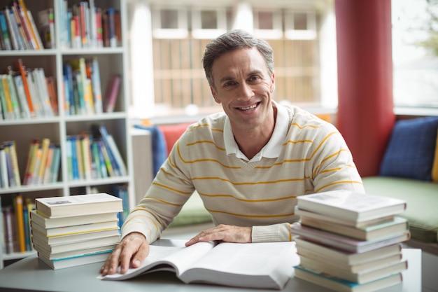 Porträt des schullehrers, der buch in der bibliothek liest Premium Fotos