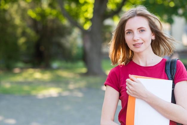 Porträt des schulmädchens mit büchern im park Kostenlose Fotos
