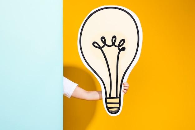 Porträt des schulmädchens mit großer glühlampe Kostenlose Fotos