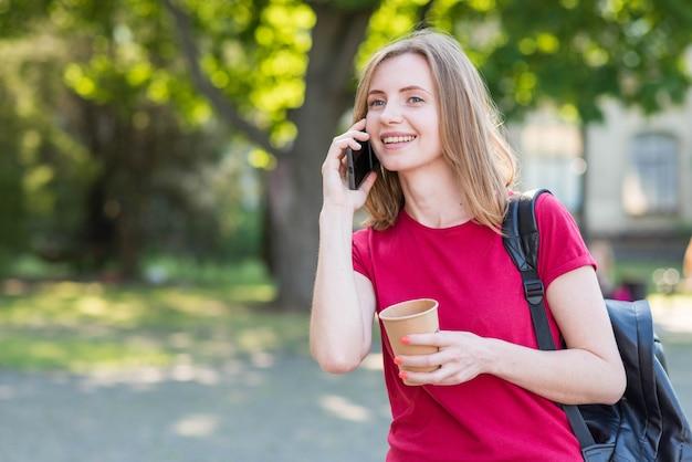 Porträt des schulmädchens telefonanruf im park tuend Kostenlose Fotos