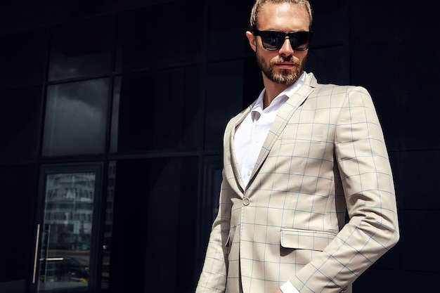 Porträt des sexy gutaussehenden mannes kleidete im eleganten beige karierten anzug an Kostenlose Fotos