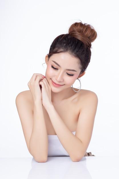 Porträt des sitzenden lächelns der attraktiven asiatischen frau auf weißem hintergrund. Premium Fotos